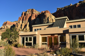 Big Modern home with brown dry mountains in the back and a desert like surrounding