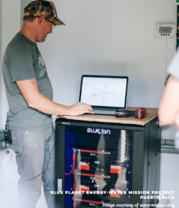 Man standing next to a battery using a computer