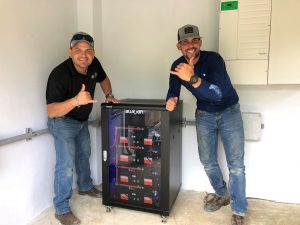 Two men giving a thumbs up next to a blue ion battery