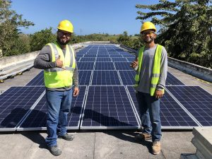 Two men posing on top of a roof after solar installation