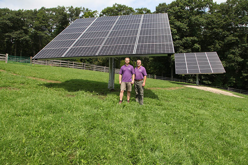 image of two people in front of solar panels
