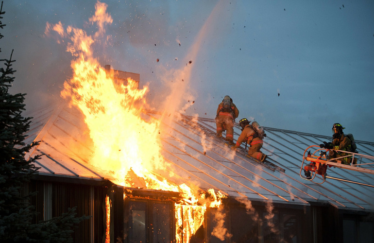 image of firefighters on burning roof