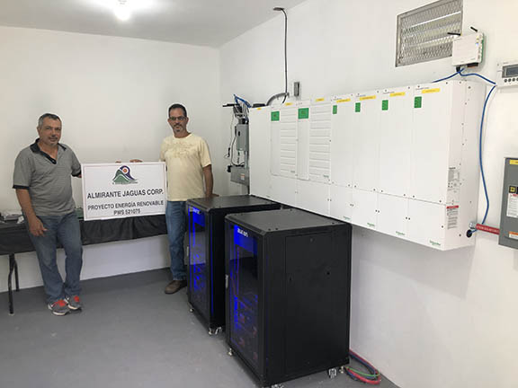 image of two people standing in front of battery systems