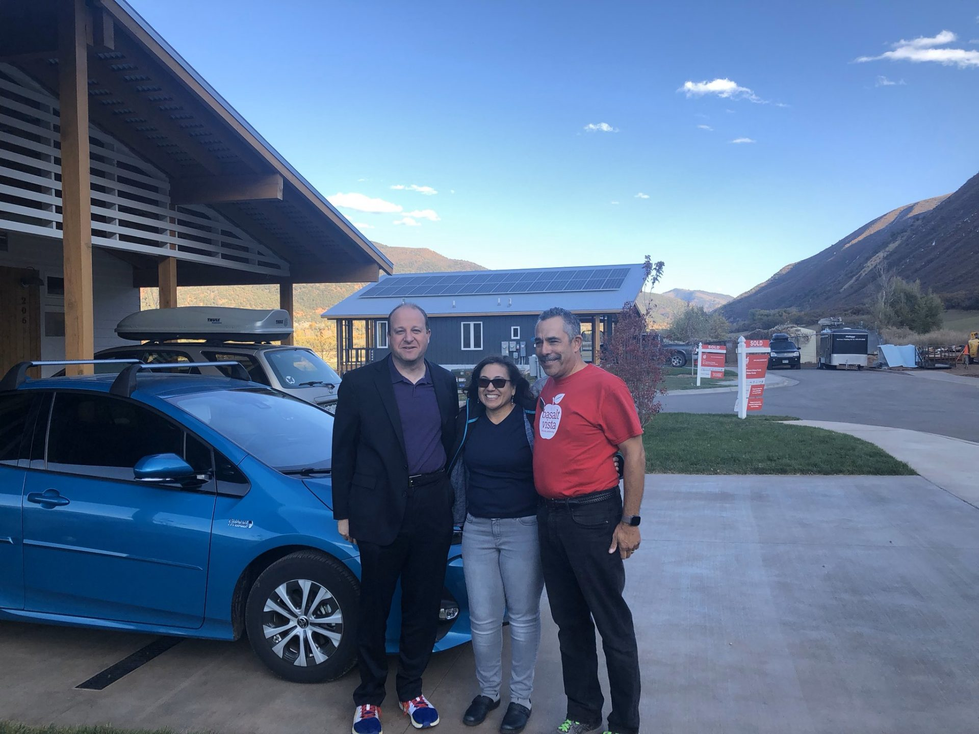 image of 3 people in front of a car