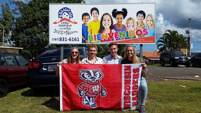 image of four people holding Wisconsin Badgers flag in front of sign in spanish