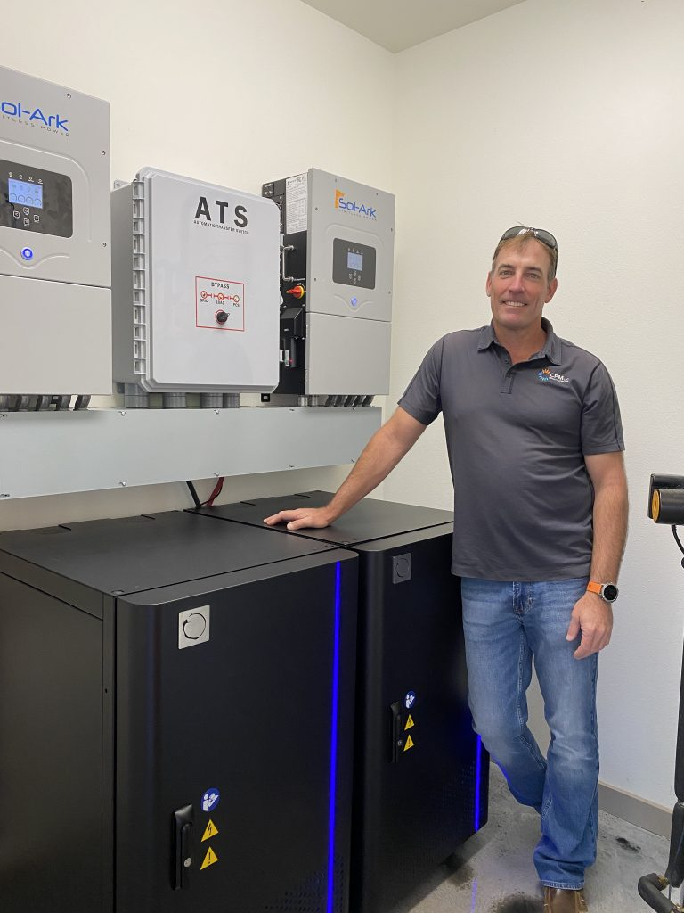 Jeff Richardson of CPM Hawaii next to (2) Blue Planet Energy Blue Ion HI energy storage systems